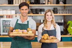 Portrait of waiter and waitress holding a tray of cupcakes Stock Photo
