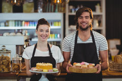 Portrait of waiter and waitress holding a tray of cupcakes Stock Photography