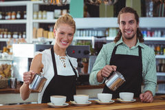 Portrait of waiter and waitress making cup of coffee at counter Stock Photography