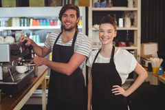 Portrait of waiter and waitress making cup of coffee at counter Royalty Free Stock Images