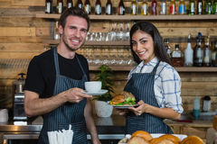 Portrait of waiter and waitresses holding cup of coffee and food at counter Stock Photo
