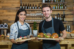 Portrait of waiter and waitresses holding cupcakes and food at counter Stock Image