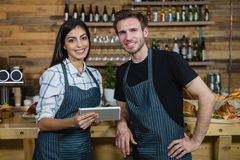 Portrait of waiter and waitresses using digital tablet at counter Royalty Free Stock Image