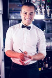 Portrait of a waiter writing down an order. In a bar Stock Photo
