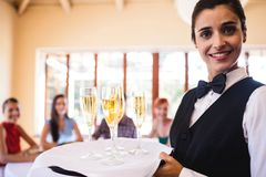 Waitress champagne glasses on tray in restaurant royalty free stock images