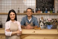 Waitress with crossed arms in coffee shop. Portrait of waitress with crossed arms standing with barista in coffee shop Stock Image