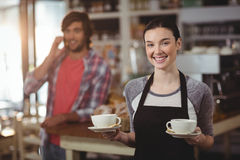 Portrait of waitress holding coffee cups Stock Photo