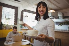 Portrait of waitress holding coffee cups with man using laptop at table Stock Photo