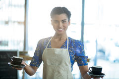 Portrait of waitress holding cup of coffee Royalty Free Stock Image
