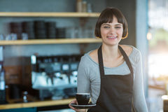 Portrait of waitress holding cup of coffee Royalty Free Stock Photography