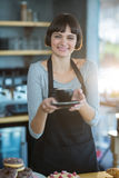 Portrait of waitress holding cup of coffee Stock Photography