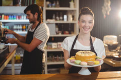 Portrait of waitress holding dessert on cake stand Stock Photography
