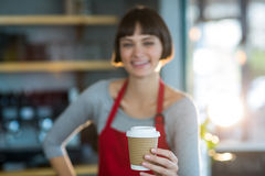 Portrait of waitress holding disposable cup of coffee Stock Image