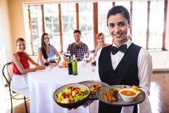 Waitress holding food on plate in restaurant. Portrait of waitress holding food on plate in restaurant stock photos