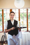 Portrait of waitress holding serving tray with champagne flutes  Royalty Free Stock Images