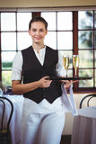 Portrait of waitress holding serving tray with champagne flutes  Royalty Free Stock Photography