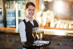 Portrait of waitress holding serving tray with champagne flutes  Stock Images