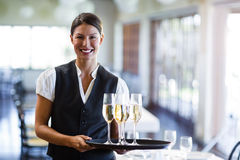 Portrait of waitress holding serving tray with champagne flutes  Stock Photos