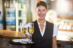 Portrait of waitress holding serving tray with champagne flutes  Stock Photo