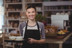Portrait of waitress holding tray of coffee cups Stock Image