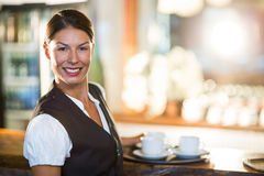 Portrait of waitress holding a tray with coffee cups Royalty Free Stock Photo