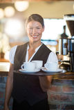 Portrait of waitress holding a tray with coffee cups Stock Photos