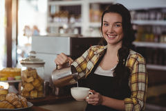 Portrait of waitress making cup of coffee at counter Stock Photo