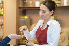 Portrait waitress serving customer at coffee shop. Portrait of a waitress serving customer at the coffee shop Royalty Free Stock Photography