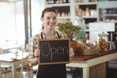 Portrait of waitress showing chalkboard with open sign Stock Photos