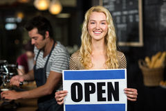 Portrait of waitress showing open sign Stock Photography