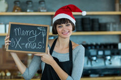 Portrait of waitress showing slate with merry x-mas sign Royalty Free Stock Photography