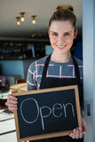 Portrait of waitress showing slate with open sign Royalty Free Stock Images