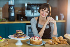 Portrait of waitress sitting at counter with sweet food on table Royalty Free Stock Photo