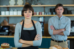 Portrait of waitress standing with arms crossed. In cafe Royalty Free Stock Images