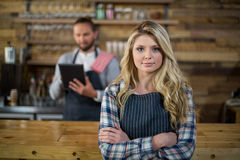 Portrait of waitress standing with arms crossed at counter. In caf Stock Images