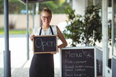 Portrait of waitress standing with chalkboard and menu Royalty Free Stock Images