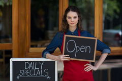 Portrait of waitress standing with chalkboard and menu Royalty Free Stock Photos