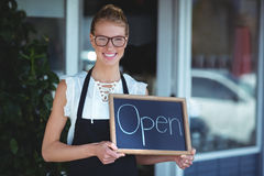 Portrait of waitress standing with chalkboard Royalty Free Stock Image