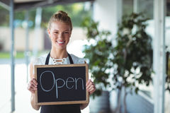 Portrait of waitress standing with chalkboard Stock Image