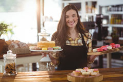 Portrait of waitress standing at counter with desserts Stock Photography