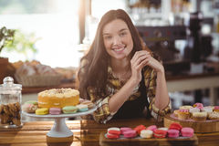Portrait of waitress standing at counter with desserts Stock Photo