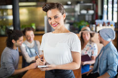 Portrait of waitress standing by customers in restaurant Stock Photos