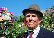 Portrait of a war veteran holding flowers. Stock Image