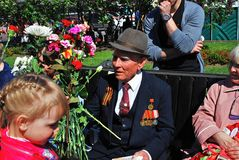 Portrait of a war veteran holding flowers. Royalty Free Stock Image