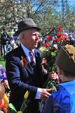 Portrait of a war veteran holding red carnation flowers. Royalty Free Stock Image