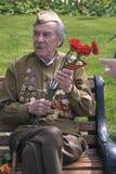 Portrait of a war veteran. He holds flowers. Stock Photo