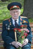 Portrait of a war veteran. He holds flowers. Stock Images