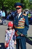 Portrait of war veteran and a teen girl, they pose for photos. Victory Day celebration in Gorky park in Moscow. Date: May 09, 2018. Color photo stock image