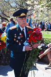 Portrait of a war veteran walking with flowers. MOSCOW - MAY 09, 2014:Portrait of a war veteran walking with flowers. Victory Day celebration in Moscow Stock Image