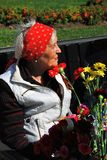 Portrait of a war veteran woman holding flowers. Royalty Free Stock Photos